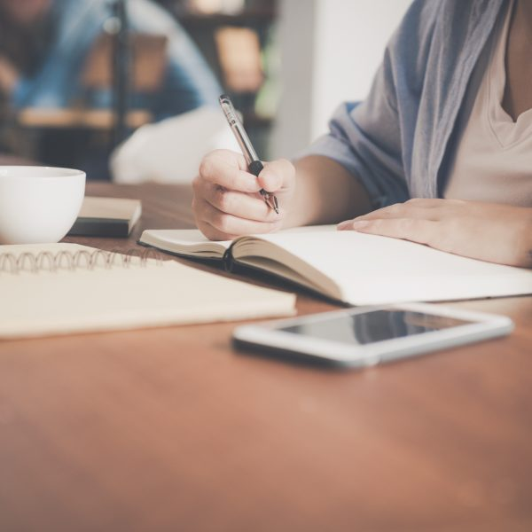 PHOTO: woman writing in a journal at a cafe